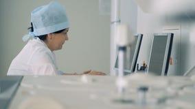 Οι εργαζόμενοι νοσοκομείων κάθονται και εργάζονται σε ένα εξοπλισμένο εργαστήριο απόθεμα βίντεο