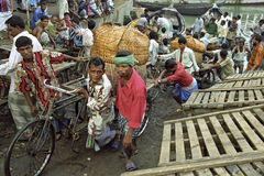 Οι εργαζόμενοι ξεφορτώνουν τις βάρκες στον πολυάσχολο λιμένα Dhaka Στοκ Φωτογραφία