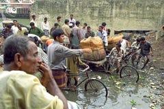 Οι εργαζόμενοι ξεφορτώνουν τις βάρκες στον πολυάσχολο λιμένα Dhaka Στοκ εικόνες με δικαίωμα ελεύθερης χρήσης