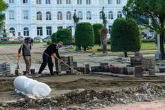 Οι εργαζόμενοι οικοδόμοι βάζουν τη νέα πλάκα επίστρωσης στη για τους πεζούς ζώνη, πεζοδρόμιο μεταξύ του πάρκου στην πόλη Στοκ εικόνα με δικαίωμα ελεύθερης χρήσης