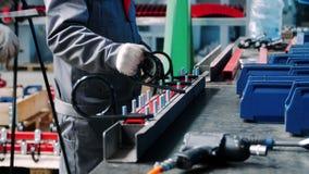 Οι εργαζόμενοι που καθορίζουν τα μέρη μετάλλων στις μονάδες στο εργαστήριο του εγχειριδίου συγκεντρώνουν φιλμ μικρού μήκους
