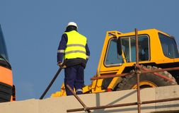 Οι εργαζόμενοι σε κίτρινο στο εργοτάξιο οικοδομής εργάζονται στα υλικά σκαλωσιάς στοκ φωτογραφία με δικαίωμα ελεύθερης χρήσης