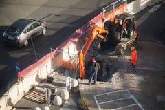 Οι εργαζόμενοι σκάβουν την τρύπα στην άσφαλτο με τον εκσκαφέα Στοκ Φωτογραφία