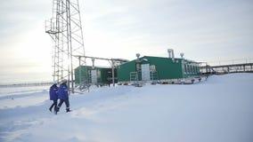 Οι εργαζόμενοι στα σκληρά καπέλα στολών πηγαίνουν να δηλητηριάσουν με αέρια τον εξαγωγικό πύργο απόθεμα βίντεο