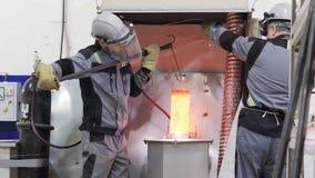 Οι εργαζόμενοι στις μάσκες λαμβάνουν έξω την καυτή μορφή και βάζουν στο πάτωμα φιλμ μικρού μήκους