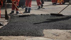 Οι εργαζόμενοι στο δρόμο επισκευάζουν την άσφαλτο απόθεμα βίντεο