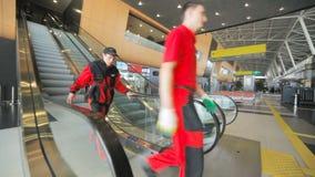 Οι εργαζόμενοι στο κόκκινο πηγαίνουν κάτω από την κυλιόμενη σκάλα στην αίθουσα αερολιμένων απόθεμα βίντεο
