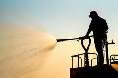 Οι εργαζόμενοι στο φορτηγό νερού ψεκάζουν το νερό στο δρόμο Στοκ εικόνες με δικαίωμα ελεύθερης χρήσης
