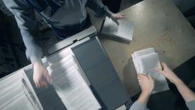 Οι εργαζόμενοι συλλέγουν το τυπωμένο έγγραφο από μια τυπογραφική γραμμή φιλμ μικρού μήκους