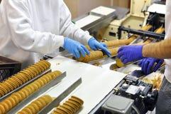 Οι εργαζόμενοι ταξινομούν τα μπισκότα σε μια ζώνη μεταφορέων σε ένα εργοστάσιο - producti στοκ εικόνες με δικαίωμα ελεύθερης χρήσης