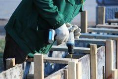 Οι εργαζόμενοι τοποθετούν τον εγκιβωτισμό για την έκχυση συγκεκριμένη και την επικεράμωση στοκ εικόνα με δικαίωμα ελεύθερης χρήσης