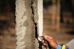 Οι εργαζόμενοι χρησιμοποιούν ένα trowel για να διακοσμήσουν τους στυλοβάτες τσιμέντου σε μια όμορφη κορυφογραμμή στοκ φωτογραφία