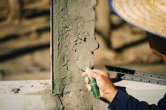 Οι εργαζόμενοι χρησιμοποιούν ένα trowel για να διακοσμήσουν τους στυλοβάτες τσιμέντου σε μια όμορφη κορυφογραμμή στοκ εικόνες