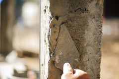 Οι εργαζόμενοι χρησιμοποιούν ένα trowel για να διακοσμήσουν τους στυλοβάτες τσιμέντου σε μια όμορφη κορυφογραμμή στοκ φωτογραφία με δικαίωμα ελεύθερης χρήσης