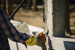 Οι εργαζόμενοι χρησιμοποιούν ένα trowel για να διακοσμήσουν τους στυλοβάτες τσιμέντου σε μια όμορφη κορυφογραμμή στοκ εικόνα
