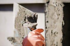Οι εργαζόμενοι χρησιμοποιούν ένα trowel για να διακοσμήσουν τους στυλοβάτες τσιμέντου σε μια όμορφη κορυφογραμμή στοκ εικόνα με δικαίωμα ελεύθερης χρήσης