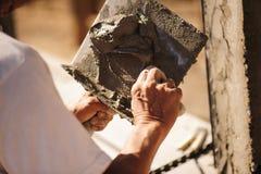 Οι εργαζόμενοι χρησιμοποιούν ένα trowel για να διακοσμήσουν τους στυλοβάτες τσιμέντου σε μια όμορφη κορυφογραμμή στοκ φωτογραφίες με δικαίωμα ελεύθερης χρήσης