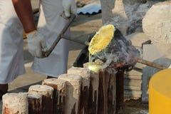 Οι εργαζόμενοι χύνουν το χρυσό στη φόρμα για να δημιουργήσουν ένα άγαλμα του Βούδα στοκ εικόνες