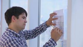 Οι εργασίες αρχιτεκτόνων με το σκίτσο, σχέδιο, προγραμματίζουν κοντά στο φωτεινό καθαρό γραφείο το πανοραμικό παράθυρο φιλμ μικρού μήκους