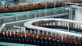 Οι εργασίες μεταφορέων ζυθοποιείων, κινούμενα μπουκάλια, κλείνουν επάνω φιλμ μικρού μήκους