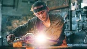 Οι εργασίες προσώπων σφυρηλατούν, θερμαίνοντας το μέταλλο στην πυρκαγιά φιλμ μικρού μήκους