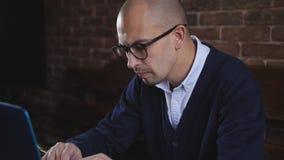 Οι εργασίες συγγραφέων για το lap-top Όμορφη μέσος-γερασμένη συνεδρίαση ατόμων στον πίνακα στην αρχή και που δακτυλογραφεί στο la φιλμ μικρού μήκους
