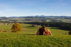 Οι ερωτευμένες παραμονές ζεύγους στην πράσινη χλόη που εξετάζει τους λόφους και τα βουνά το φθινόπωρο, από το όμορφο αγροτικό τοπ Στοκ Φωτογραφίες
