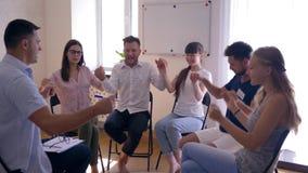 Οι ευτυχείς άνθρωποι κρατούν τα χέρια κατά τη διάρκεια της συνόδου θεραπείας στη συνεδρίαση ψυχολόγων στις καρέκλες φιλμ μικρού μήκους