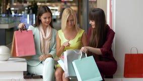 Οι ευτυχείς αγορές, ελκυστικά κορίτσια με πολλές τσάντες έχουν τη διασκέδαση με τις αγορές τους καθμένος στη λεωφόρο κατά τη διάρ φιλμ μικρού μήκους