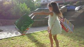 Οι ευτυχείς αγορές, το παιδί αγοραστών στα γυαλιά ηλίου και το μοντέρνο φόρεμα με τις συσκευασίες μερών περιστρέφουν στο χορτοτάπ απόθεμα βίντεο