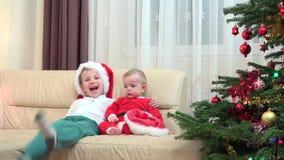 Οι ευτυχείς αδελφοί αγκαλιάζουν το στενό χριστουγεννιάτικο δέντρο γέλιου χαμόγελου, κοστούμι Santa απόθεμα βίντεο