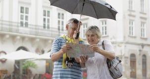 Οι ευτυχείς ανώτεροι τουρίστες στέκονται κεντρικός και απολαμβάνουν το βροχερό καιρό σε Lviv απόθεμα βίντεο