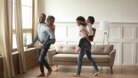Οι ευτυχείς αφρικανικοί γονείς piggyback το παιχνίδι γέλιου παιδιών στο σπίτι απόθεμα βίντεο
