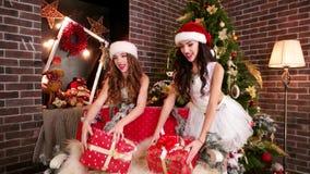 Οι ευτυχείς αδελφές γιορτάζουν το νέο έτος, στο νέο έτος τα κορίτσια δωματίων στα κοστούμια διακοπών προετοιμάζουν τα δώρα, που π απόθεμα βίντεο