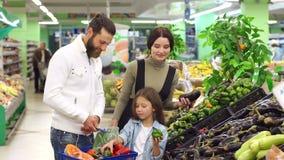 Οι ευτυχείς γονείς με ένα παιδί επιλέγουν τα φρέσκα λαχανικά και τα βάζουν σε ένα καλάθι απόθεμα βίντεο