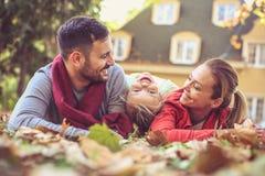 Οι ευτυχείς γονείς με την τοποθέτηση μικρών κοριτσιών στο έδαφος, θέτουν στη κάμερα Στοκ Εικόνα