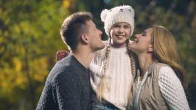 Οι ευτυχείς γονείς φιλούν την εύθυμη κόρη στο πάρκο φθινοπώρου, πλούσια οικογένεια, ευημερία απόθεμα βίντεο