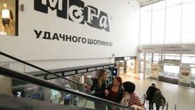 Οι ευτυχείς γυναίκες ανυψώνουν επάνω στη γρήγορη κυλιόμενη σκάλα στη λεωφόρο αγορών απόθεμα βίντεο
