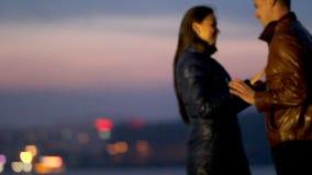 Οι ευτυχείς εραστές αγκαλιάζουν στα πλαίσια μιας πόλης νύχτας φιλμ μικρού μήκους