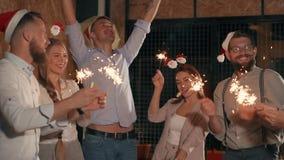 Οι ευτυχείς εργαζόμενοι γραφείων παίζουν με τα sparklers στη γιορτή Χριστουγέννων φιλμ μικρού μήκους