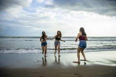 Οι ευτυχείς και συγκινημένες νέες ασιατικές κινεζικές γυναίκες που απολαμβάνουν έχοντας τη διασκέδαση στην όμορφη παραλία ηλιοβασ στοκ εικόνα