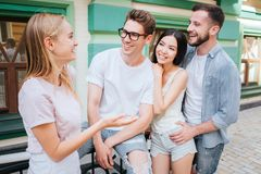 Οι ευτυχείς και satisfieds νεαροί άνδρες και οι γυναίκες στέκονται μαζί στο πράσινο κτήριο Το ξανθό κορίτσι εξετάζει τους φίλους  Στοκ φωτογραφία με δικαίωμα ελεύθερης χρήσης