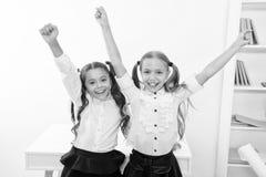 Οι ευτυχείς μαθητές κρατούν τα χέρια επάνω στη σχολική τάξη, έννοια νίκης Τα μικρά κορίτσια γιορτάζουν τη νίκη Είμαστε οι νικητές στοκ φωτογραφία
