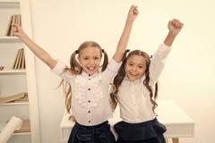 Οι ευτυχείς μαθητές κρατούν τα χέρια επάνω στη σχολική τάξη, έννοια νίκης Τα μικρά κορίτσια γιορτάζουν τη νίκη Είμαστε οι νικητές στοκ εικόνα