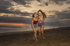 Οι ευτυχείς νέες αδελφές ή το ασιατικό κινεζικό κορίτσι στην παραλία ηλιοβασιλέματος με το καλύτερο φίλο της που έχει τη διασκέδα στοκ εικόνες