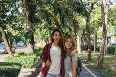 Οι ευτυχείς νέες ασιατικές γυναίκες συνδέουν να παίξουν ο ένας στον άλλο ενώ κάνουν το ταξίδι πόλεων στοκ εικόνες με δικαίωμα ελεύθερης χρήσης