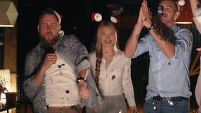 Οι ευτυχείς νέοι έχουν τη διασκέδαση στη νύχτα Χριστουγέννων, πετώντας το κομφετί φιλμ μικρού μήκους