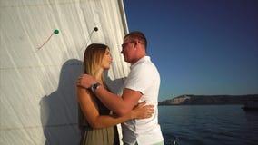 Οι ευτυχείς νέοι εραστές αγκαλιάζουν σε ένα σκάφος αναψυχής στην ηλιόλουστη ημέρα απόθεμα βίντεο