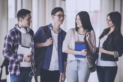 Οι ευτυχείς νέοι σπουδαστές μιλούν στην αίθουσα στοκ εικόνα