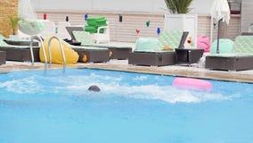 Οι ευτυχείς νέοι στα κοστούμια λουσίματος στέκονται με τη ρόδινη διογκώσιμη σφαίρα δαχτυλιδιών και παραλιών κοντά swimming-pool απόθεμα βίντεο